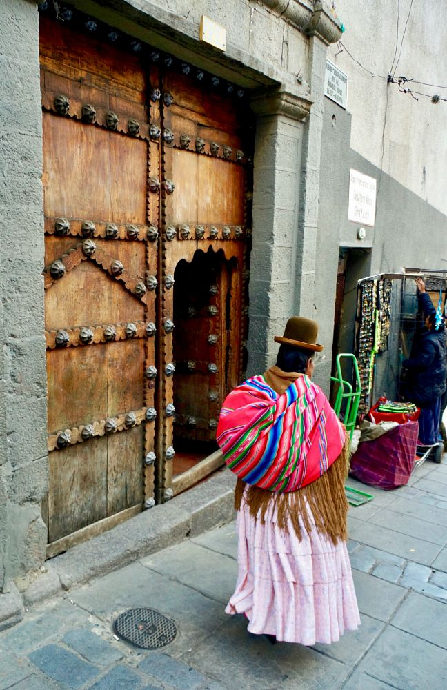 Photo in People #bolivia #doorway #wooden door #culture #la paz #tradition #city #street photography #travel #south america #street #woman #vacation #destination #adventure