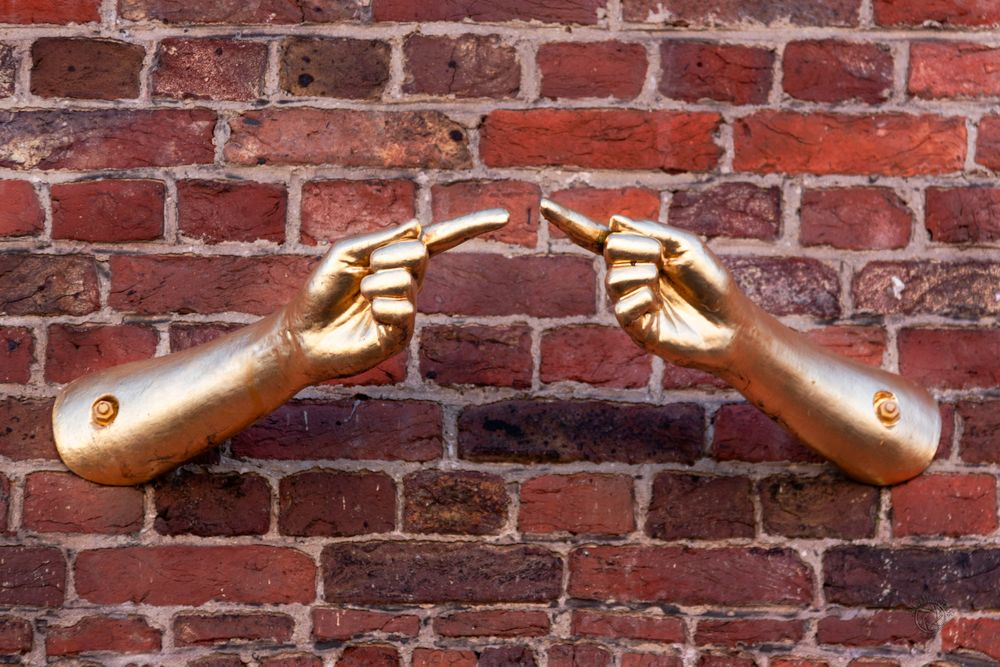 Photo in Architecture #red #wall #sculptor #hand #finger #brick #gold #point at