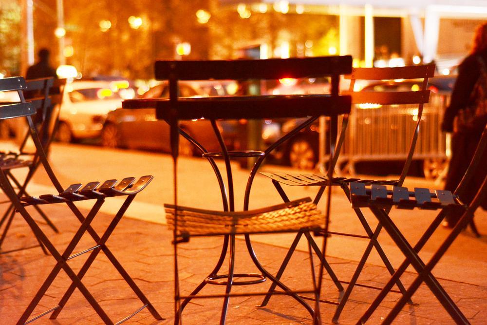 Photo in Street Photography #street #city #urban #sidewalk #avenue #ny #new york #night #chair #light #winter #hiliday #car #cold #weather #nikon #bokeh #orange #cafe