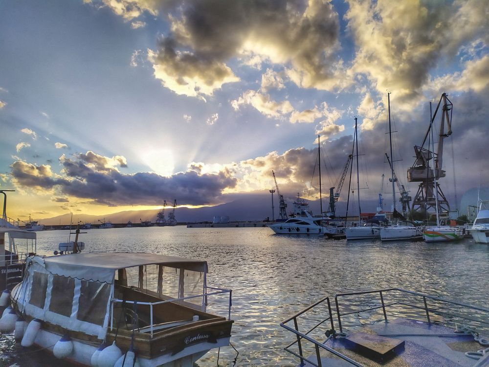 Photo in Random #crane #sunset #port #clouds #sun rays #boats #sea