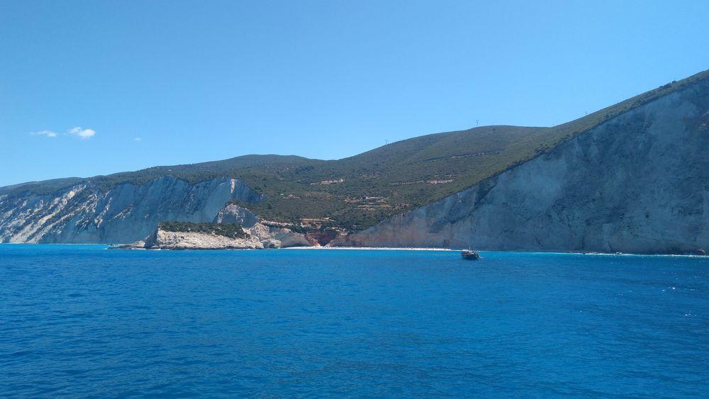 Photo in Sea and Sand #sea #blue #water #shore #beach #rocks #green #boat #porto katsiki #sky #sunshine #relaxation #beautiful #nature #summer
