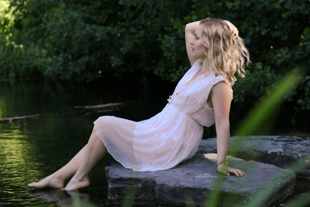 Photo in Portrait with model Eileen Mary #lake #sun #water #girl #model #woman #availablelight #seaside #sommer #bonde #rose #stones #portrait #dress #barefeet