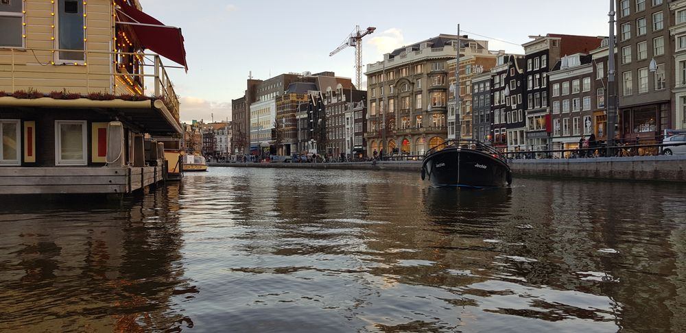 Photo in Cityscape #canal #amsterdam #europe #travel #netherlands #boat #sea #water #buildings #street #crane #clouds #sky #air