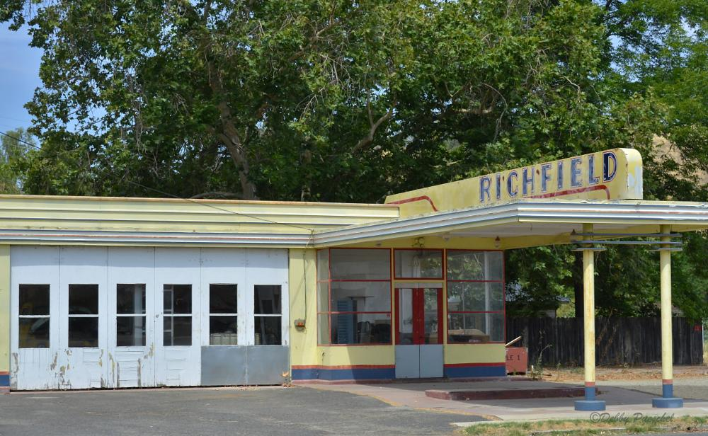 Photo in Rural #richfield gas station #adandoned #colors of yellow red and blue #small town #boasted of having a richfield #old station #car bay #oak tree giving shade