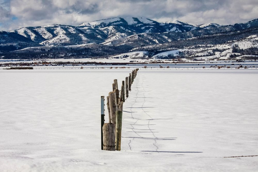 Photo in Landscape #winter #cold #fence #shadow #snow #sun #clouds #mountains #idaho