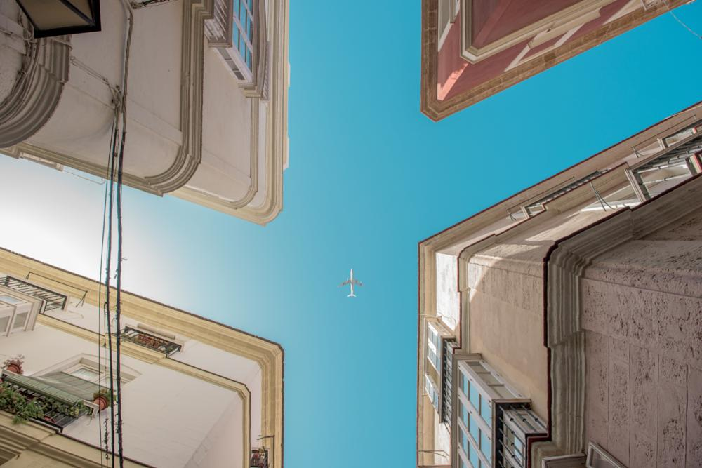 Photo in Street Photography #street #sky #airplane #spain #europe #andalucia #cadiz #building #lookup #blue #intersection #sun #composition #streetphotography #streetcontest