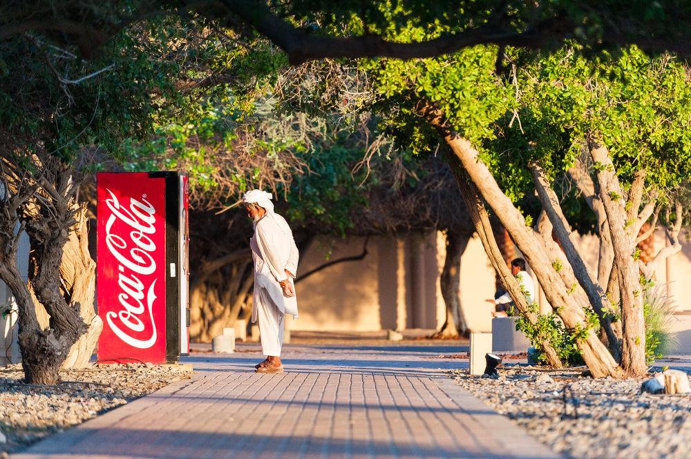 Photo in People #nikon #al ain #zoo #old #man #curiosity #coca #cola #coca cola #vending #soda #f/2.8 #d700 #70-200mm