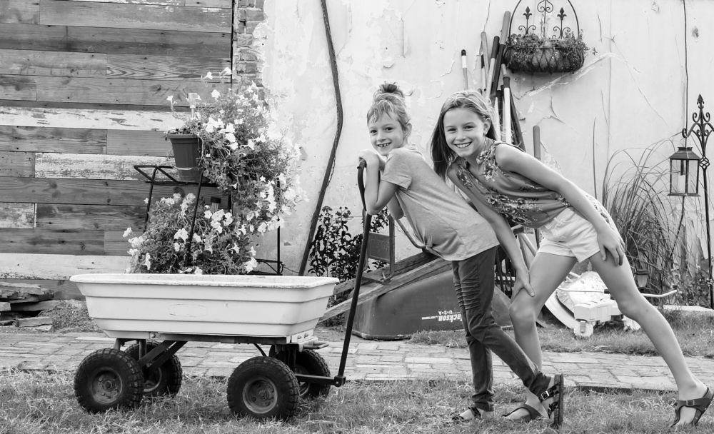 Photo in Black and White #b&w #sisters #wagon #outdoors #siblings #girls #plants #portrait