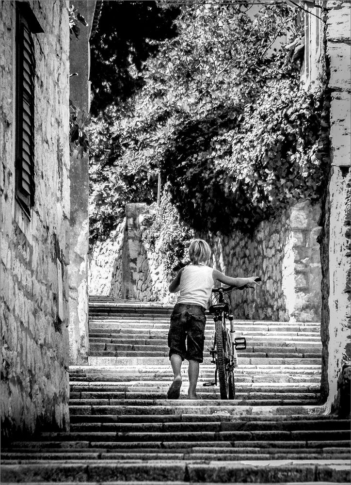 Photo in Street Photography #boy #street #a bicycle #street stairway #b&w