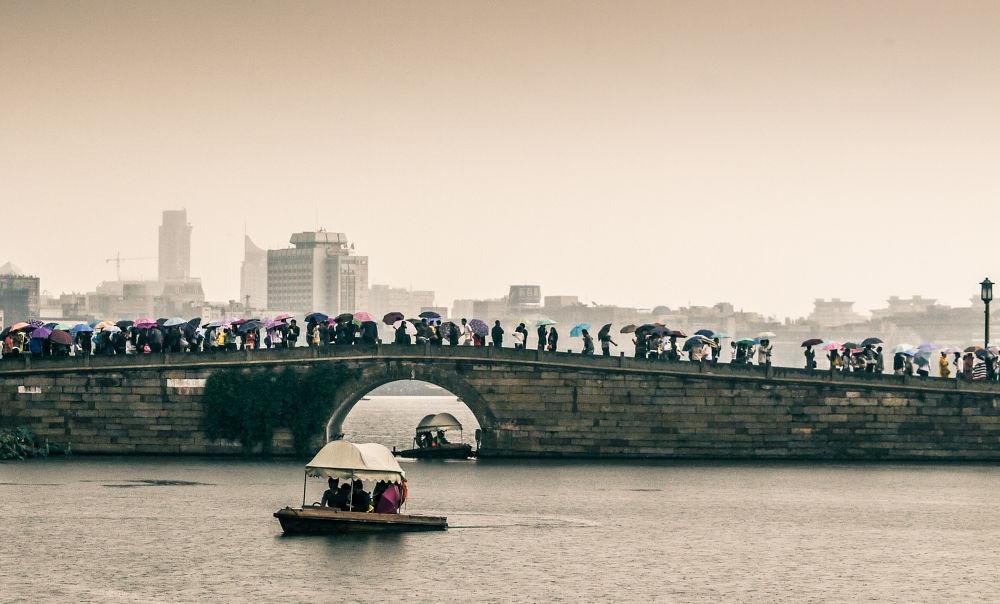 Photo in Random #water #bridge #lake #rain #boat #china #umbrella #lumix #gf1 #zhejiang #hangzhou #west lake