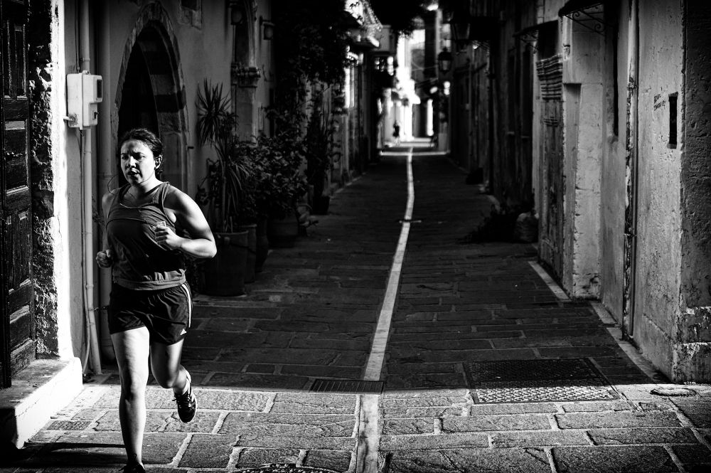 Photo in Street Photography #mono #monochrome #b&w #b&w photography #street #street photography #candid #candid photography #rethymno #crete #greece #35mm #sel35f18 #woman #running