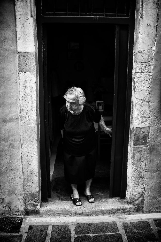 Photo in Street Photography #mono #monochrome #b&w #b&w photography #lady #old lady #old woman #woman #looking #door #20mm #sel20f28 #sony nex #nex-6 #street #street photography #portrait #portraiture #candid #candid photography #rethymno #crete #greece