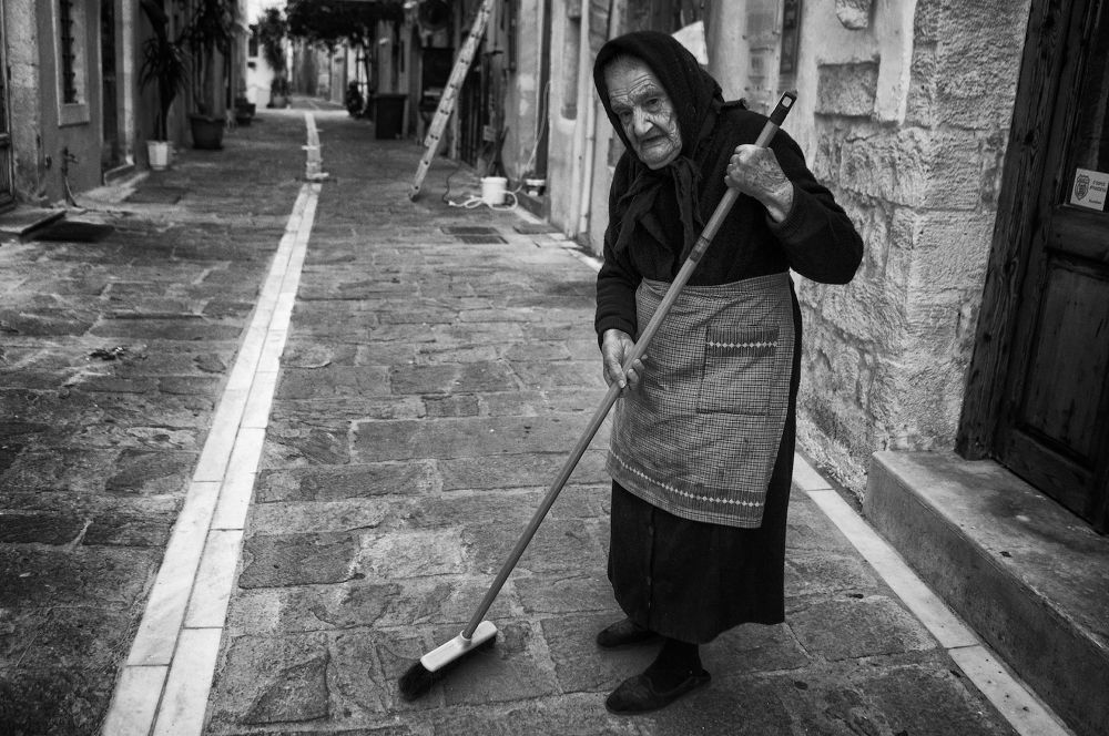 Photo in Street Photography #mono #monochrome #street hunters #street photography #candid photography #portrait #street portrait #old lady #old woman #sweeping #rethymno #crete #greece #b&w #b&w photography #20mm #sel20f28 #sony nex #nex-6