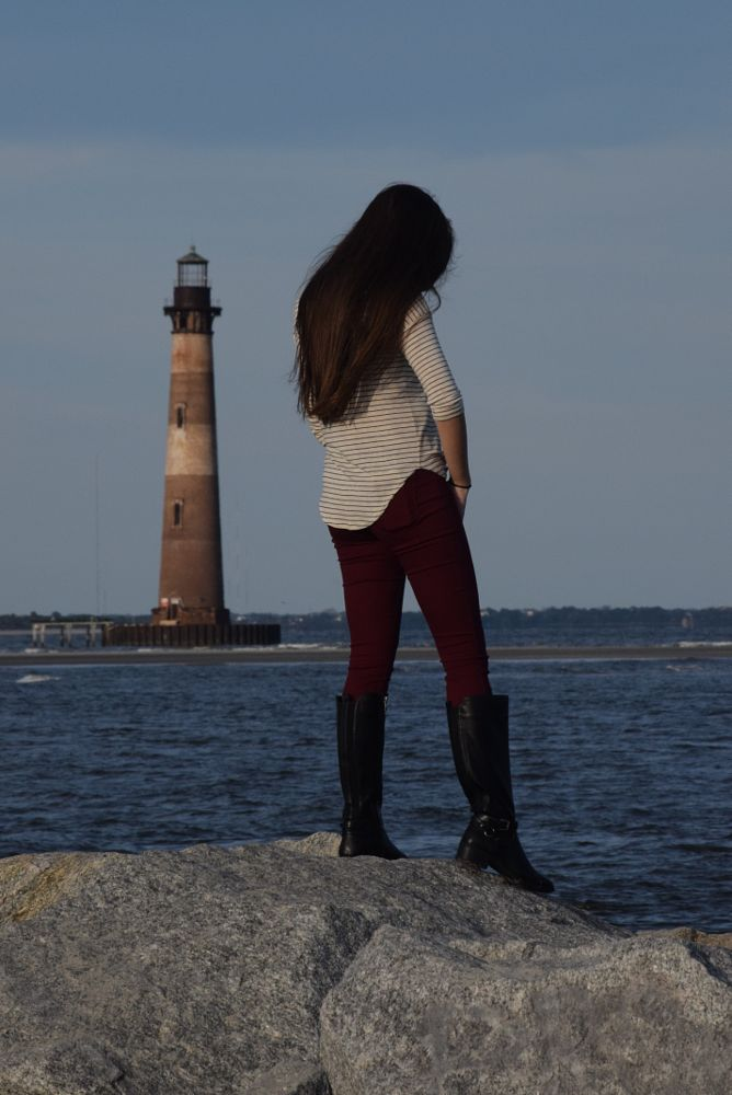 Photo in Sea and Sand #lighthouse #lighthouse and girl #girl standing on rocks