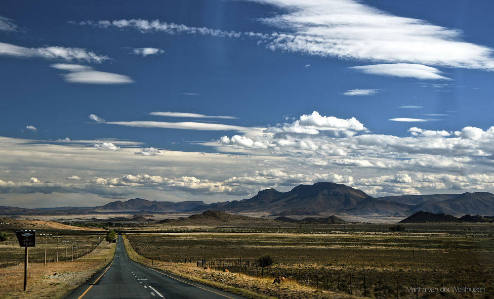 Photo in Landscape #forlorn #space #open #flat #landscape #mountains #clouds #solitary road