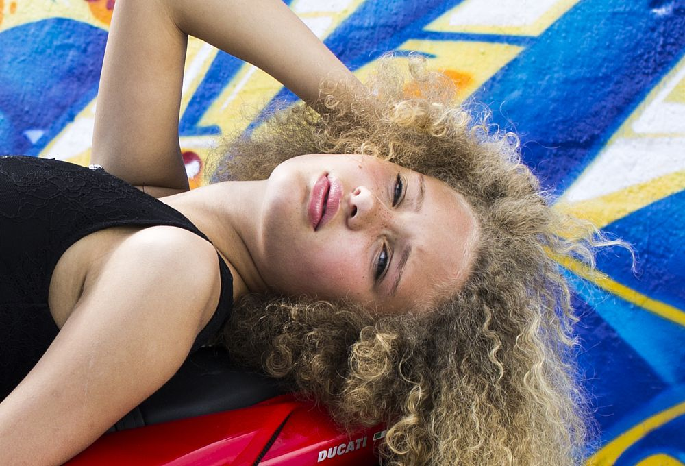 Photo in Portrait #model #black dress #curly hair #pretty #girl #female #motorcycle #red #blue #black #brown #yellow #graffiti #outdoors #harbor