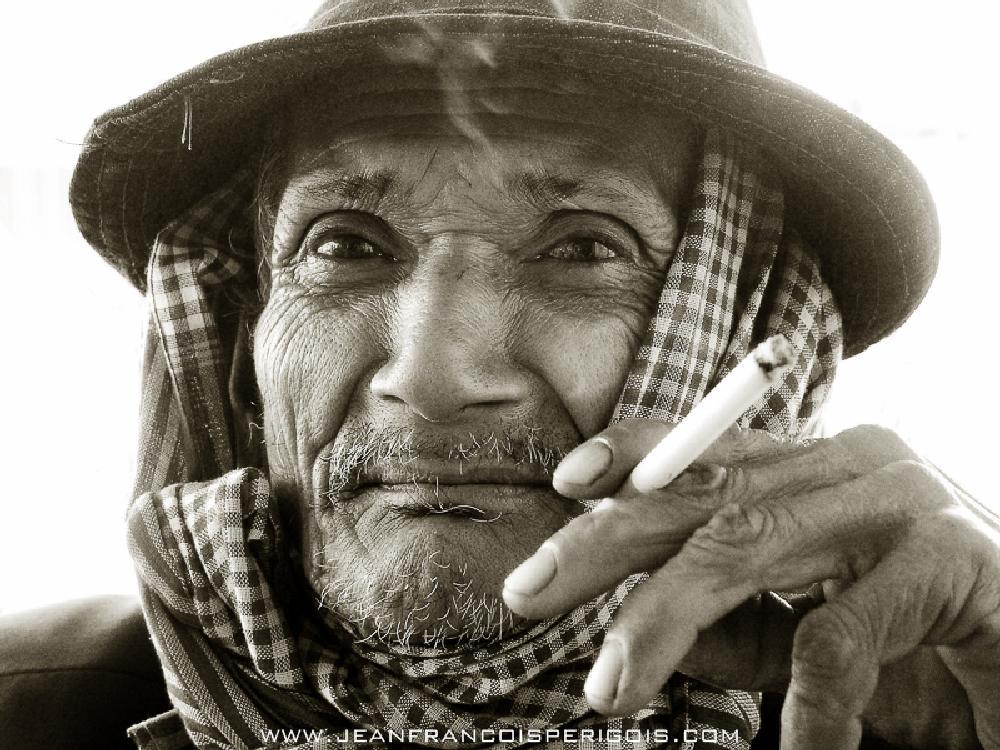 Photo in Portrait #man #asia #asian #face #portrait #eyes #wise #wisdom #cigarette #krama #cambodia #black and white #good life #beautiful #happy #smoke #health