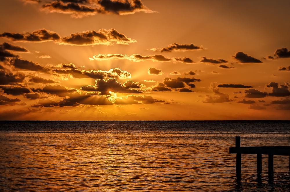 Photo in Sea and Sand #sunset #landscape #ocean #water #dock #clouds #orange #honduras #roatan #west bay #west end #sea #sun