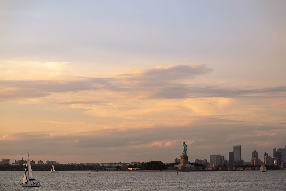 Photo in Landscape #colors #light #sky #clouds #sunset #glow #dusk #twilight #water #hudson river #new york harbor #waterfront #buildings #skyscrapers #boats #sailboats #sailing #sails #monument #statue of liberty #outdoors #leisure #nature #beauty #tourism #street photography