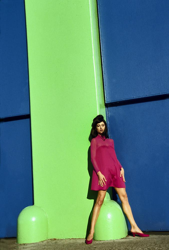 Photo in Street Photography #woman #sunning herself against #a green pillar #with red dress