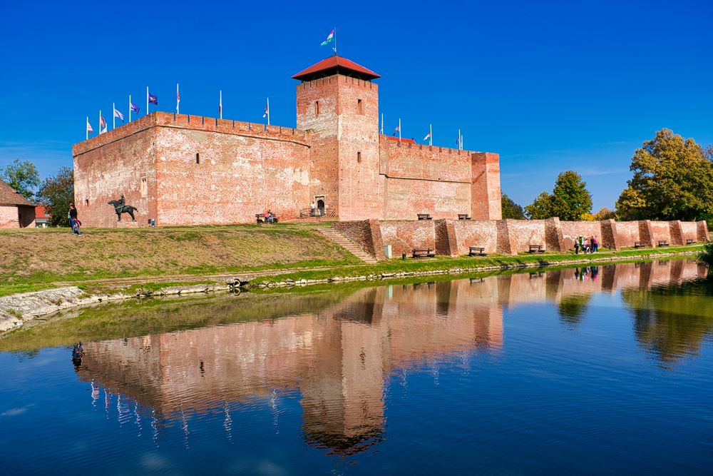 Photo in Travel #brick castle #castle #clear sky #blue #lake #reflection #history #tower #renaissance #medieval #fortified wall #fortress #fort