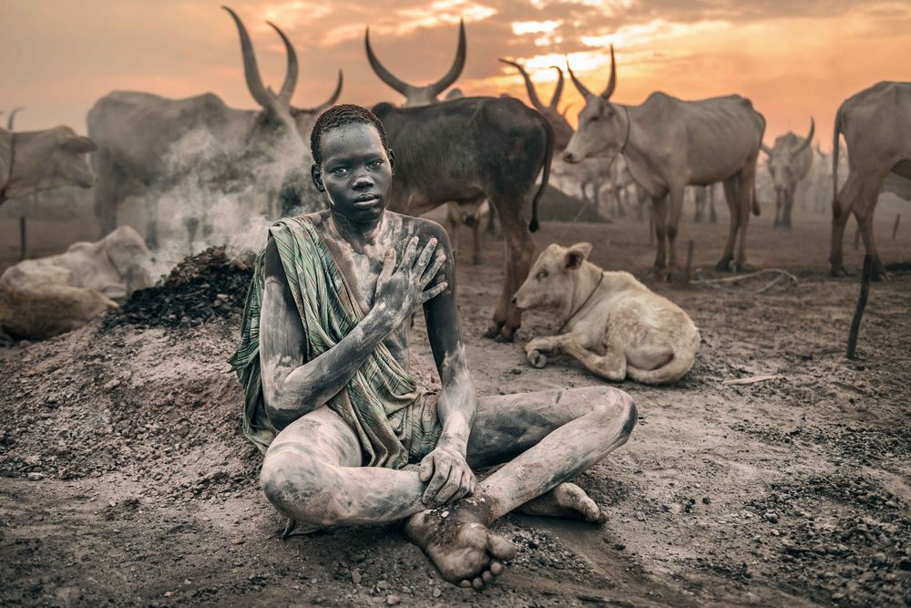 Photo in Portrait #sitting #warming up #dust #ash #cattle camp #mundari #africa #south sudan #terekeka #boy #people #portrait #street photography #place #culture #one person #full length #sunrise #cloud #looking at camera #african ethnicity #outdoor #tribal #village #nature #nikon