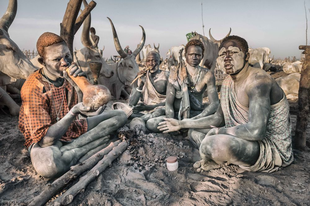 Photo in People #animal #sitting #sunset #cattle camp #cattle #mundari #smoke #rifle #africa #south sudan #terekeka #men #people #portrait #street photography #place #culture #three persons #full length #cloud #sun #looking at camera #african #ethnicity #outdoor #caw #bull #tribal #village #horn #mammal #nature #nikon