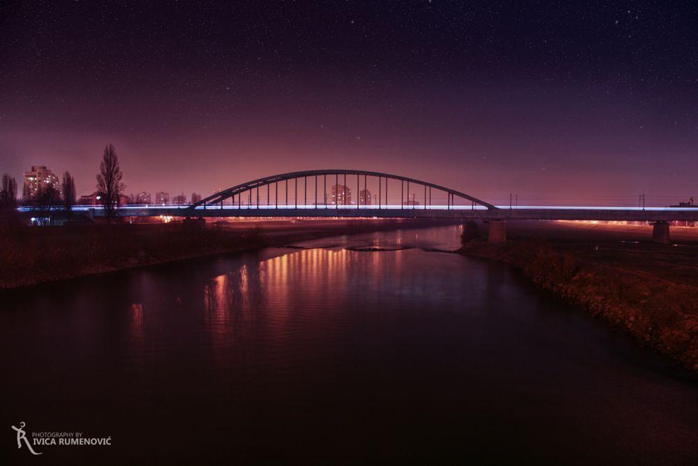 Photo in Cityscape #zagreb #croatia #night #sky #clouds #train #longexpohunter #longexposion #river #bridge #stars #city #lights