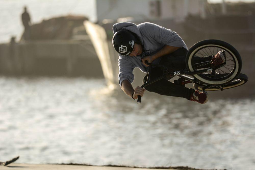 Photo in Sports #city #sea #water #blue #light #bicycle #sport #jump #bike #high #wheels #sports