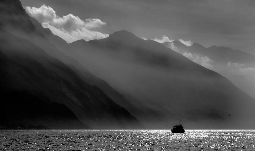 Photo in Random #lakegarda #italy #scenic #landscape #mountains #water #lake #boat #bnw #blackandwhitephotography #bw #nikond5200 #clouds #europe