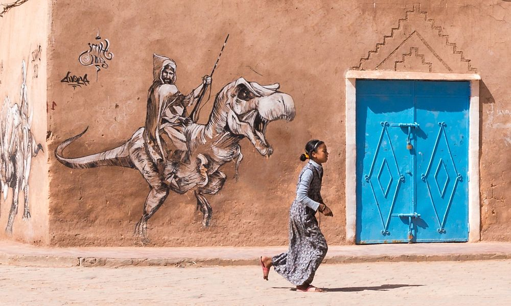 Photo in Street Photography #morocco #young girl #dinosaur #street photo #street art #blue #ouarzazate #door #ocre