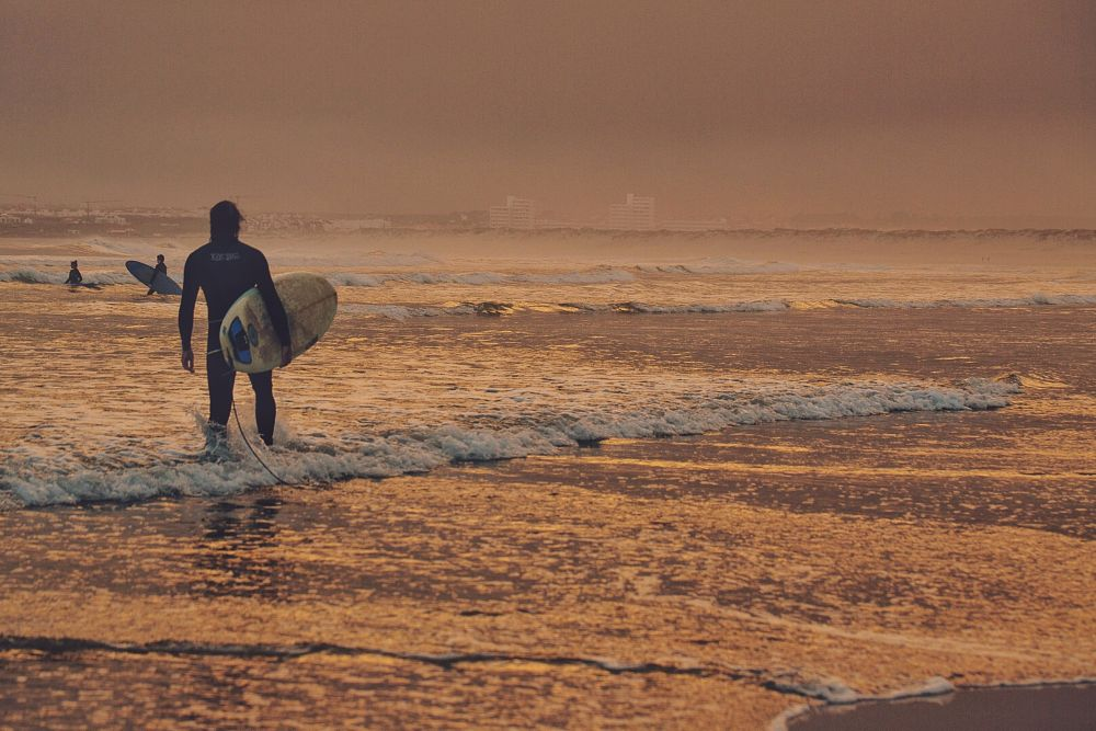 Photo in Sea and Sand #surfer #sunset #beach #beachlife #travel #waves #ocean #surf #water sports #orange #storm clouds