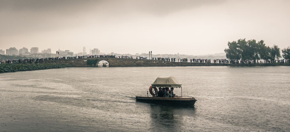 Photo in Random #river #water #lake #rain #boat #people #china #umbrella #fog #mist #cloudy #panasonic #lumix #gf1 #zhejiang #hangzhou #west lake